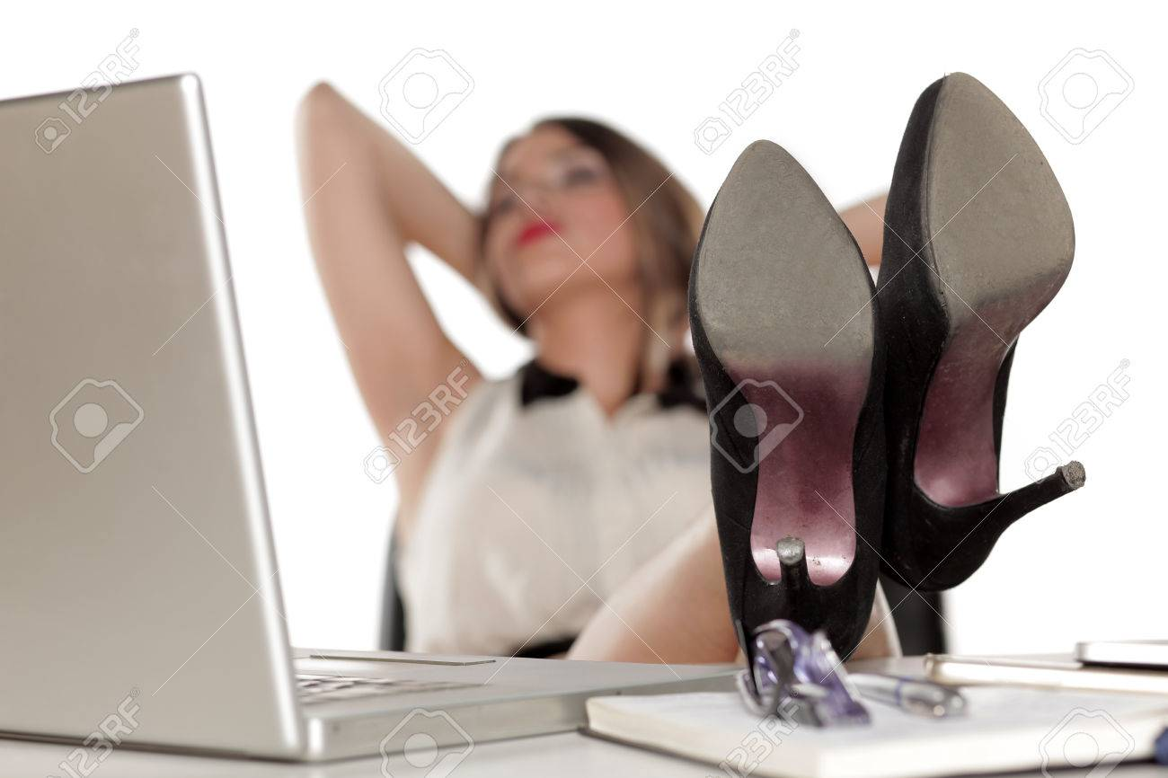 8262737337ae03 Stock Photo - Tired business woman resting at her desk with her legs on the  table