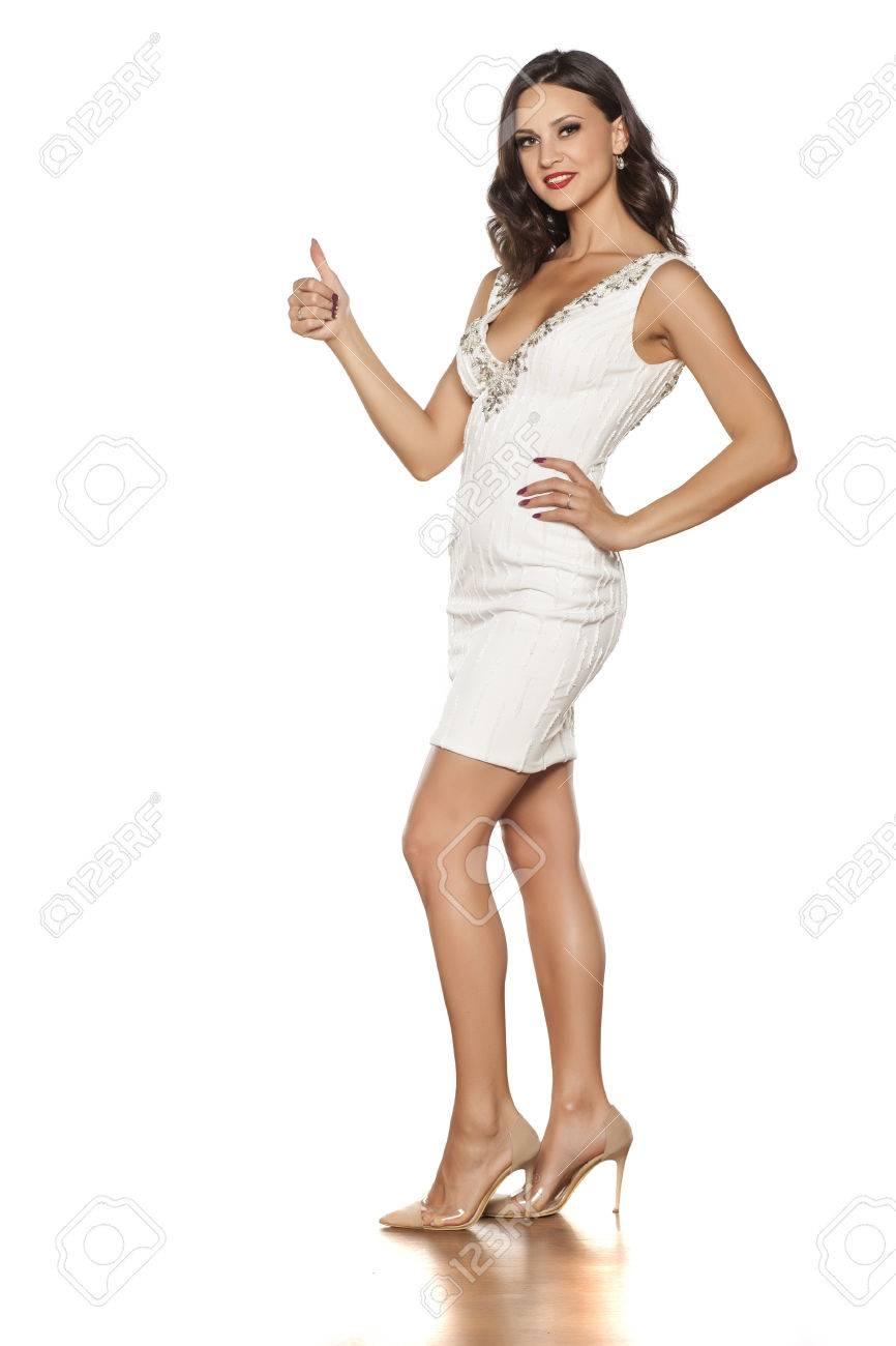 Sonriente Mujer Joven Y Bella En Vestido Corto Elegante Y Zapatos De Tacón Alto Que Muestra Los Pulgares Para Arriba