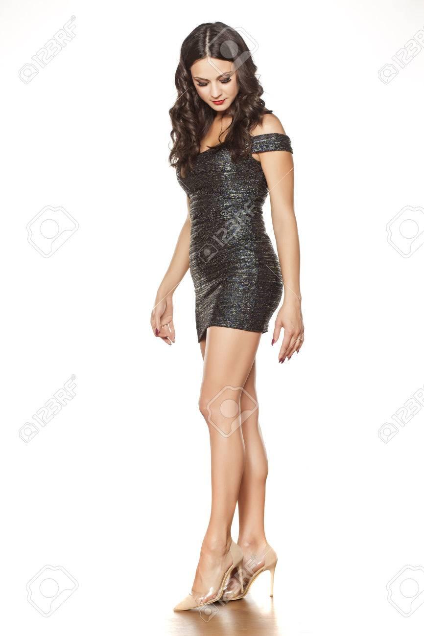 83875697422 Banque d images - Belle jeune femme en robe courte élégante et talons hauts  debout sur blanc