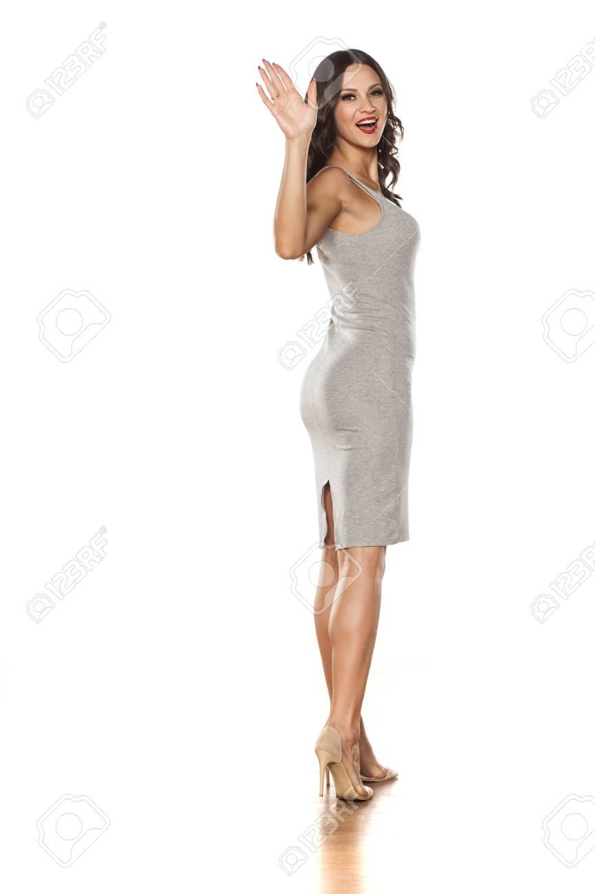 Joven Y Bella Mujer Posando En Un Vestido Corto Y Zapatos De Tacón Alto Y La Mano Que Agita