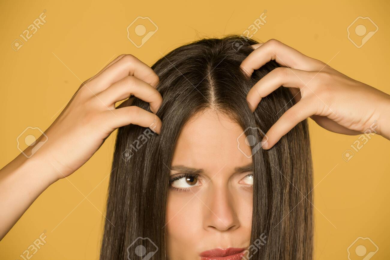 Beautiful young woman with itchy scalp on yellow background - 129450782