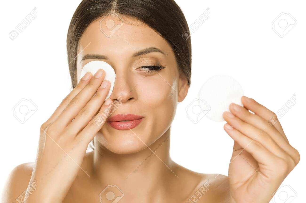 Young beautiful woman claning her face with cotton pad on white background - 134205169