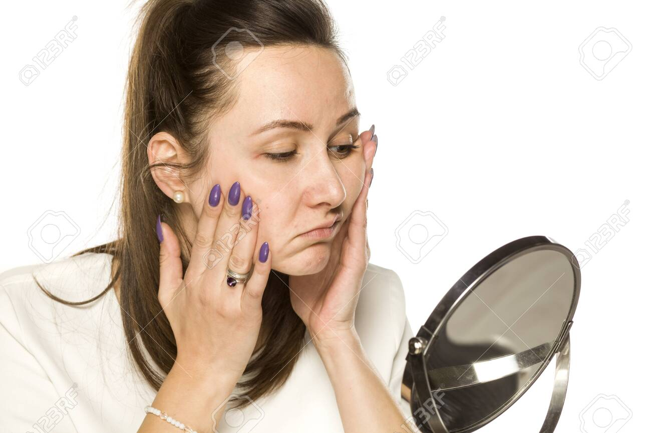 bored woman looking at herself in the mirror on white background - 141354733