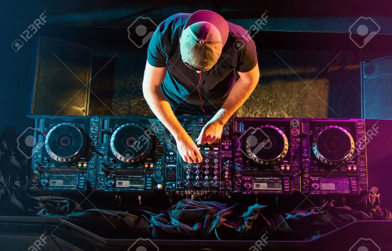 Handsome DJ playing on CD players during party. - 76049297