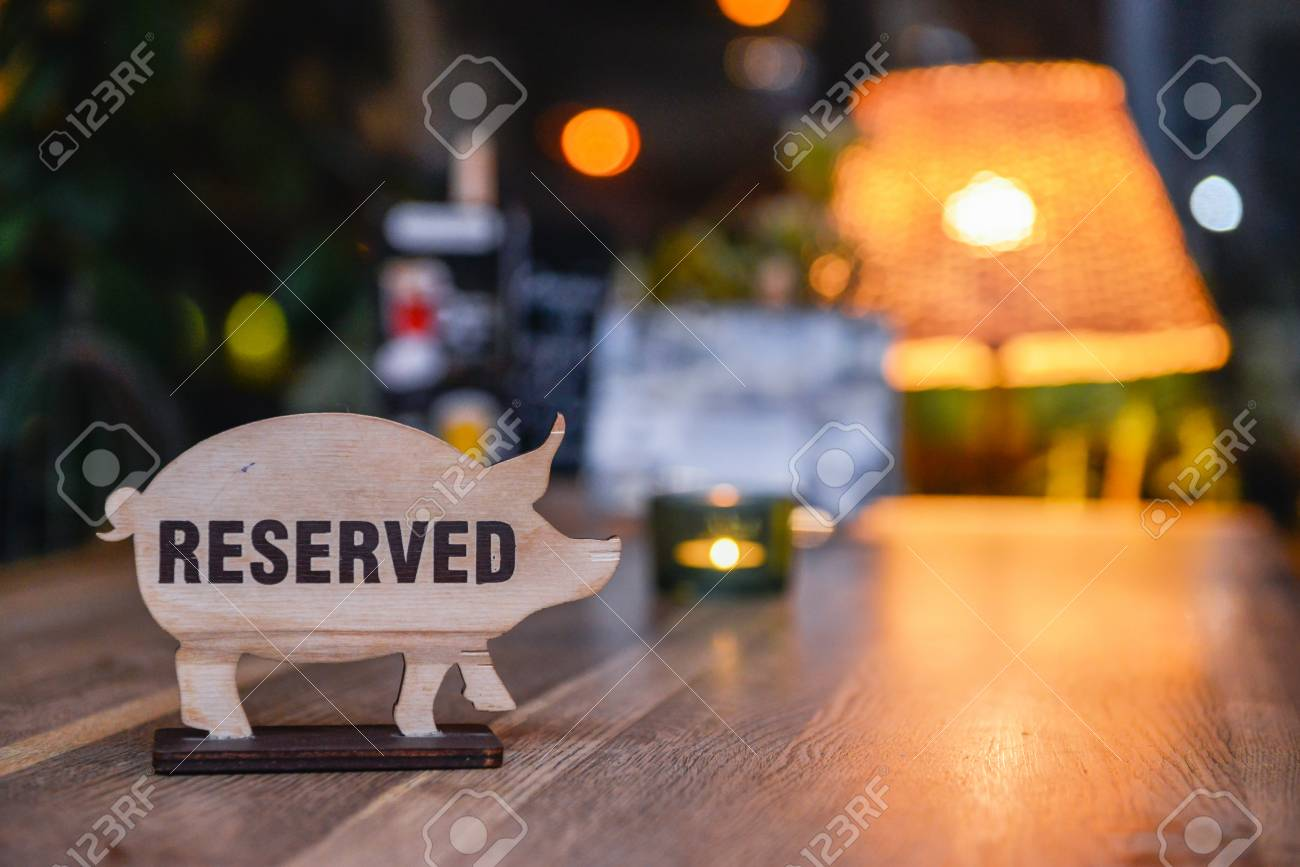 Reserved sign on a restaurant table. Sign in the form of pigs - 97136235
