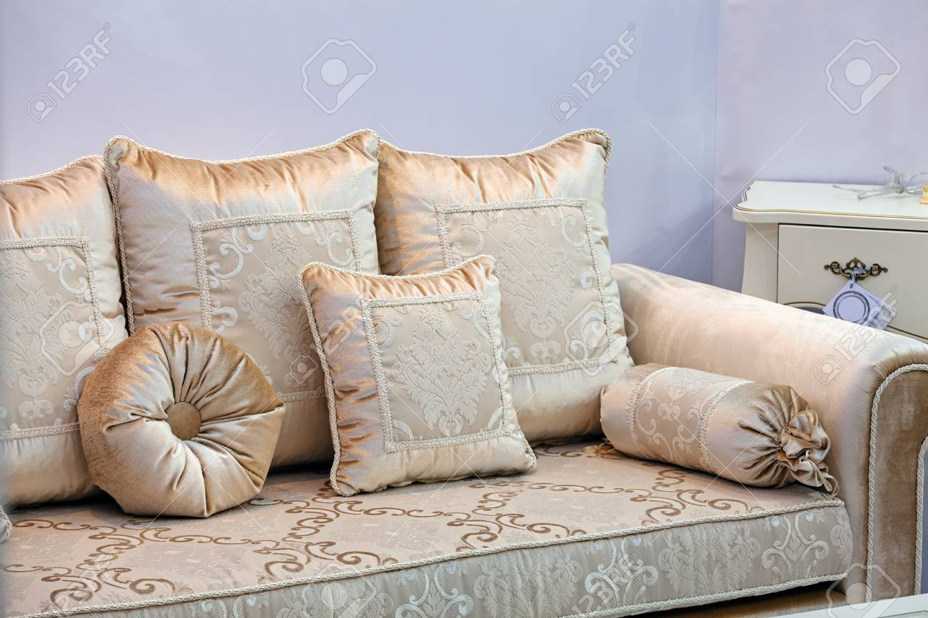 Beautiful modern gold sofa with pillows for living room