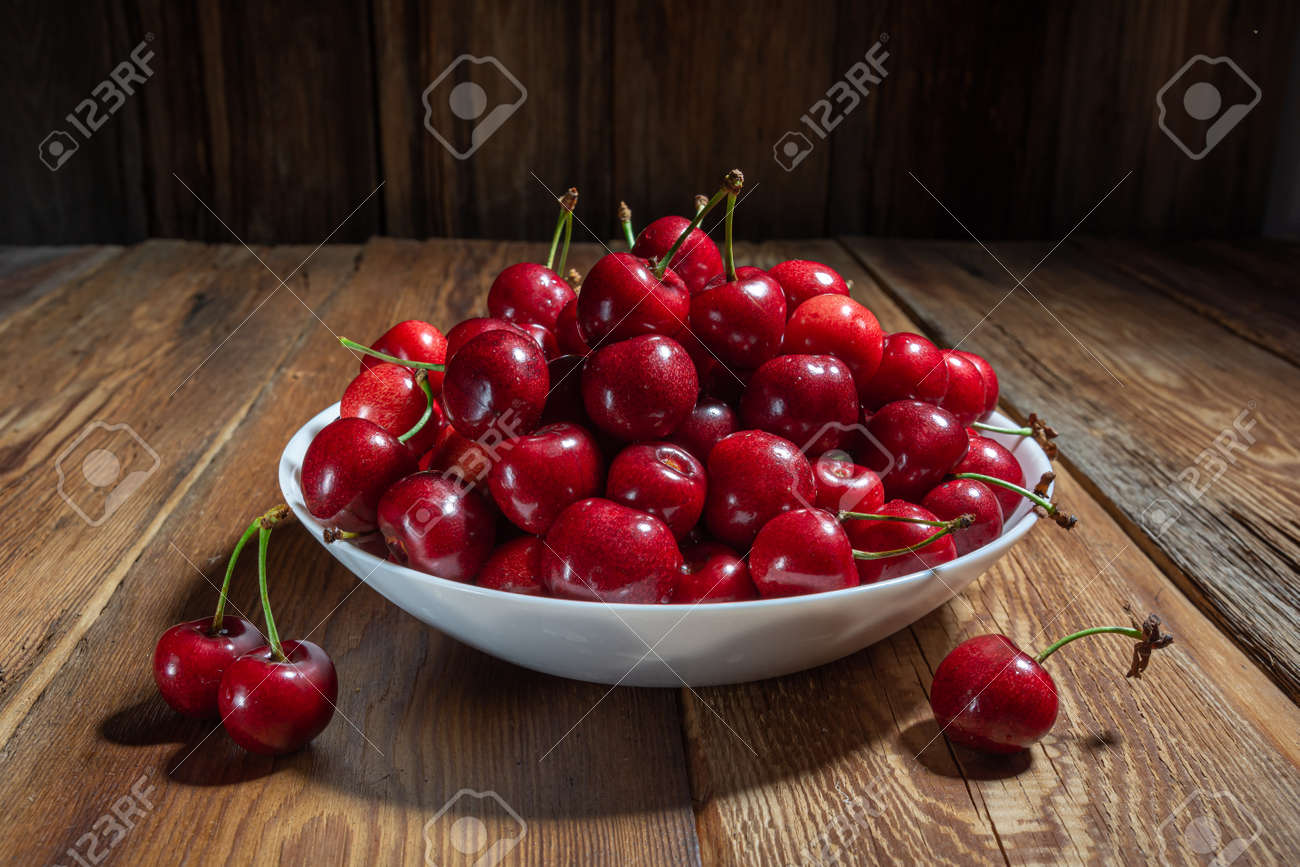 fresh, juicy cherries in a plate on a wooden table close-up, rustic style, horizontal view - 150181589