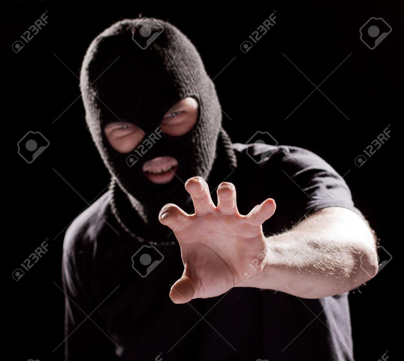 Burglar in mask, robbing and catching something by hand Stock Photo - 10834661