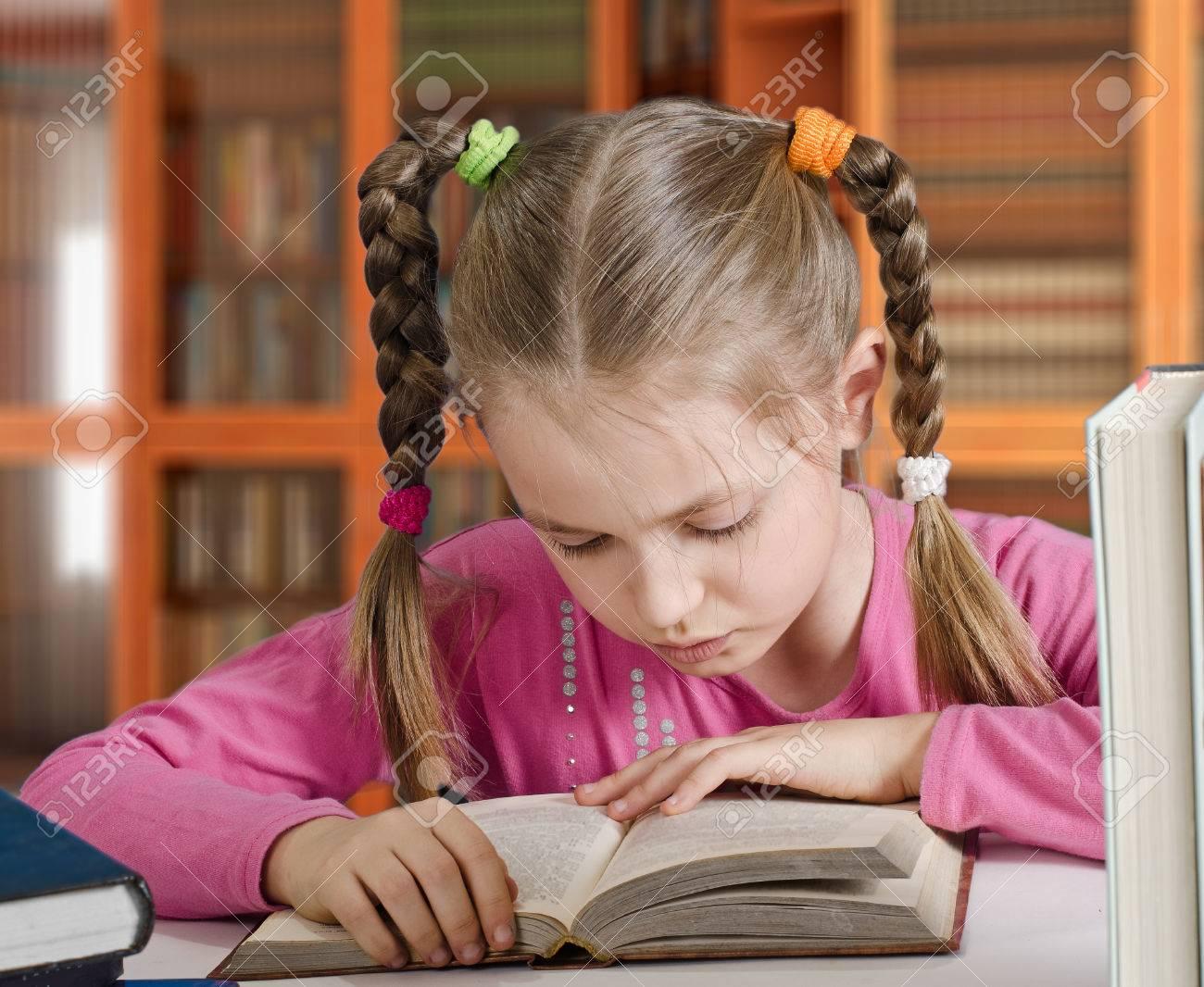 La Jeune Fille De 9 Ans Avec Deux Tresses Lit Le Livre La Photo Contre Les Bibliotheques