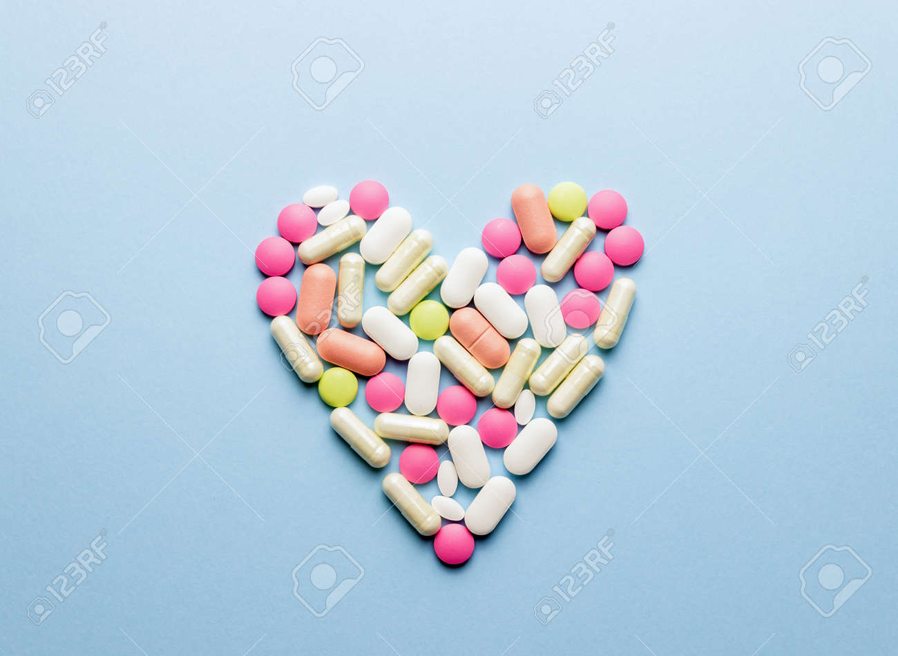 The heart is laid out of pills on a blue background. Health. Medicine. Pharmacy. - 154536881