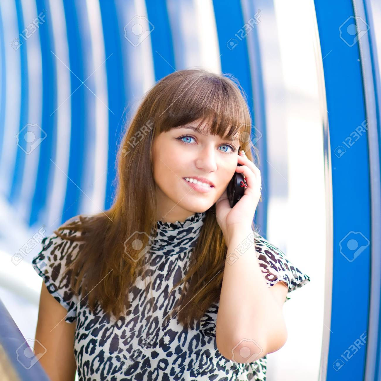 Beautiful confident businesswoman indoor glass corridor talking by phone Stock Photo - 5407163