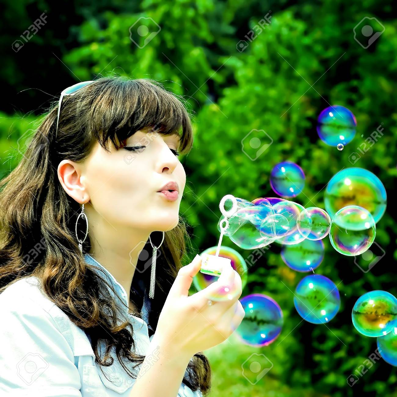 Young girl blowing soap bubbles in summer green park Stock Photo - 5887039