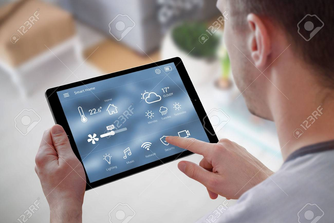 Smart home control on tablet. Interior of living room in the background. - 58852762
