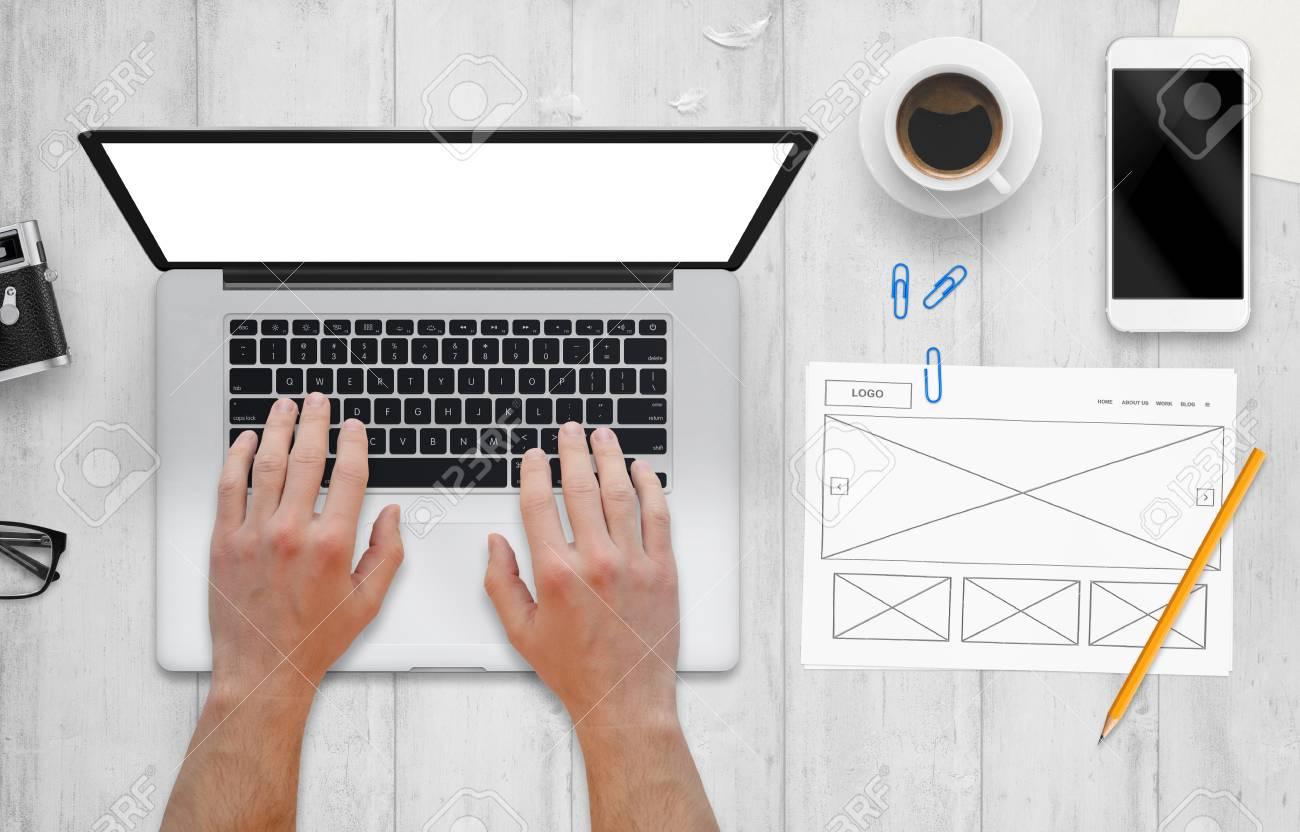 web designer work on computer plan of web site drawn on paper