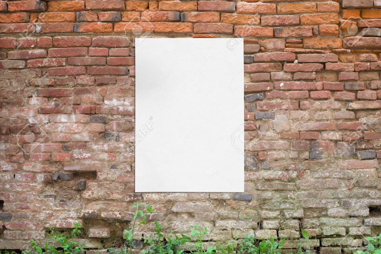 Poster glued to old brick wall. Blank, clean white paper for mockup, design presentation - 135249146