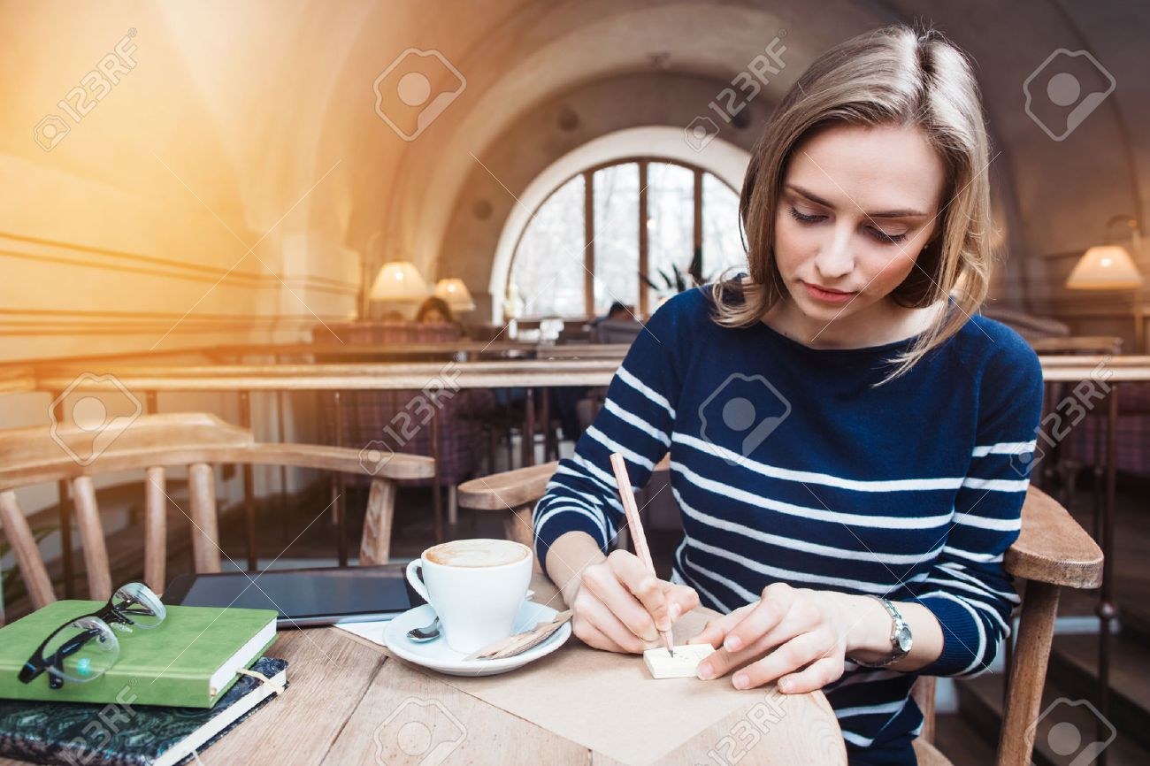 Young attractive woman writes reminders on stickies in cafe. Concept of planning personal traning schedule Foto de archivo - 74673927