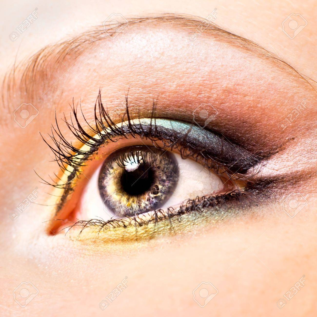 Close-up of beautiful womanish eye with yellow and green make-up - 10285141
