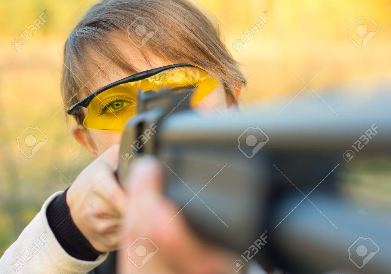 A young girl with a gun for trap shooting and shooting glasses aiming at a target Stock Photo - 15812447