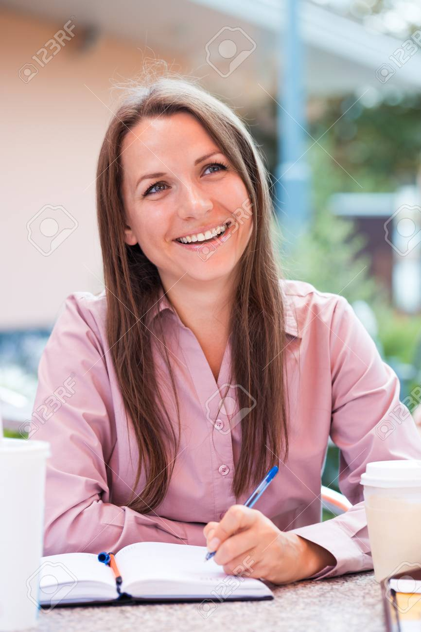 Smiling businesswoman sitting in a cafe and writing in notepad Stock Photo - 22484875