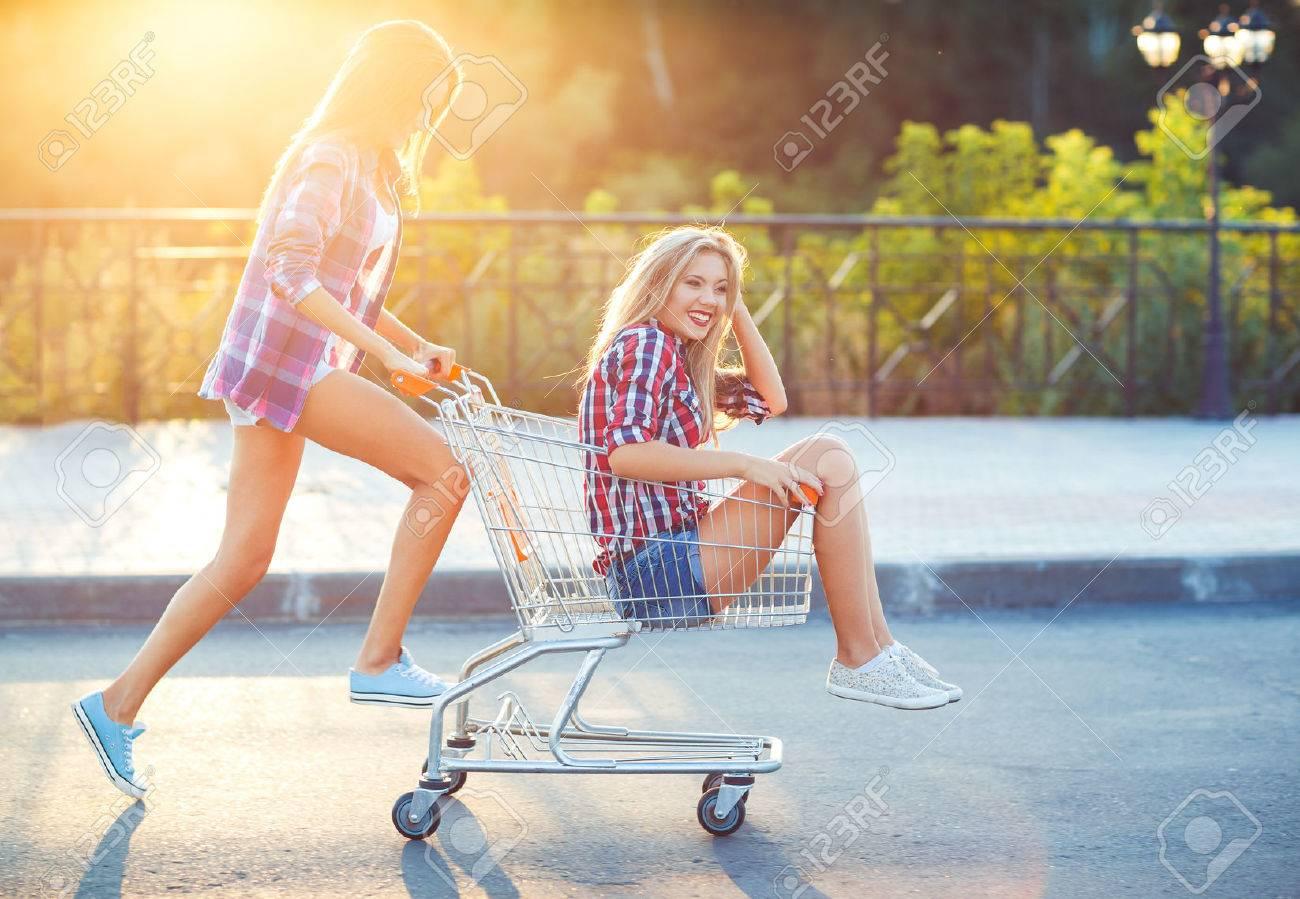 Two happy beautiful teen girls driving shopping cart outdoors - 41087595