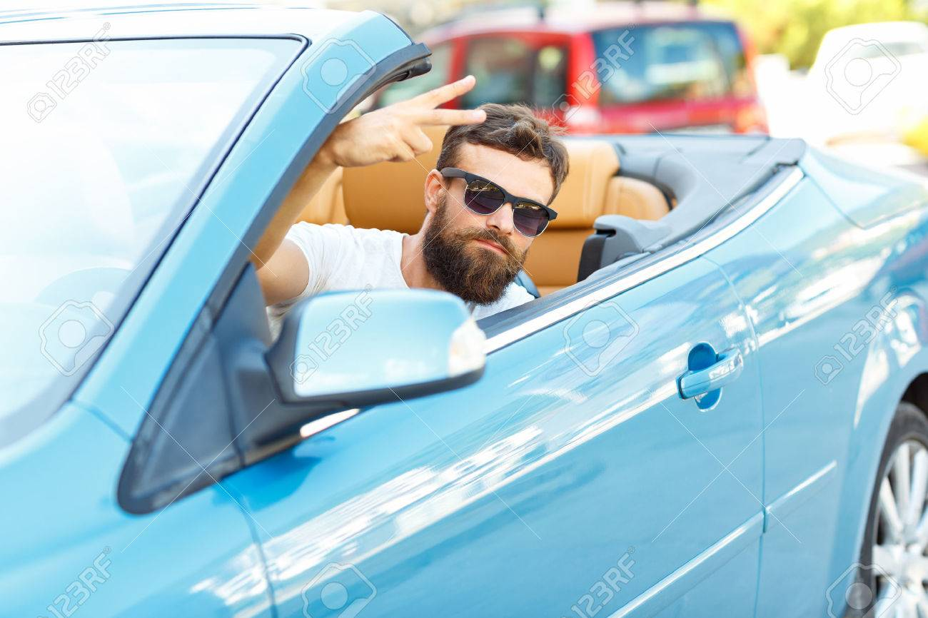A young bearded man sitting in a convertible - - the concept of buying a used car or a rental car - 48229593