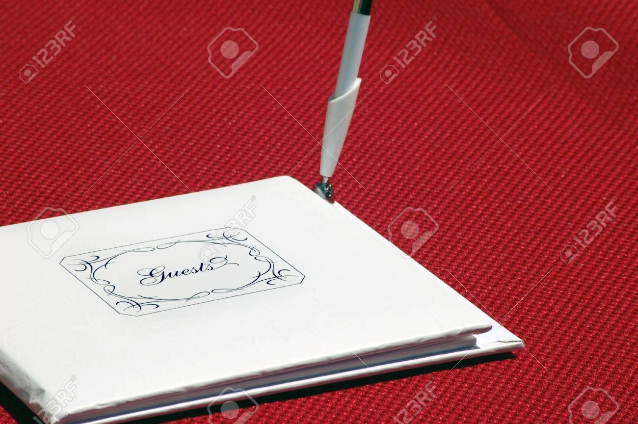 Livre D Or Blanc Ferme Qui Dit Invites Sur Le Devant Avec Un Stylo Debout Sur Le Cote C Est Sur Une Nappe Rouge