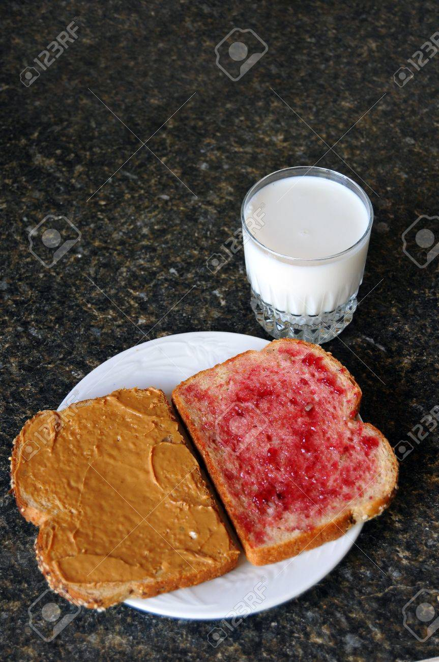Open peanut butter and jelly sandwich on a counter top with a glass of milk beside the plate Stock Photo - 6814061