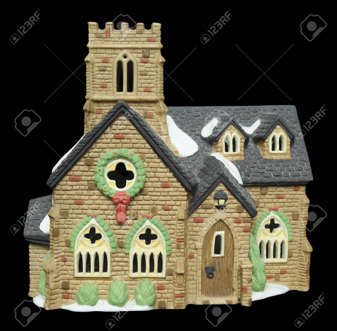 A Miniature Ceramic Church With Christmas Decorations And Snow