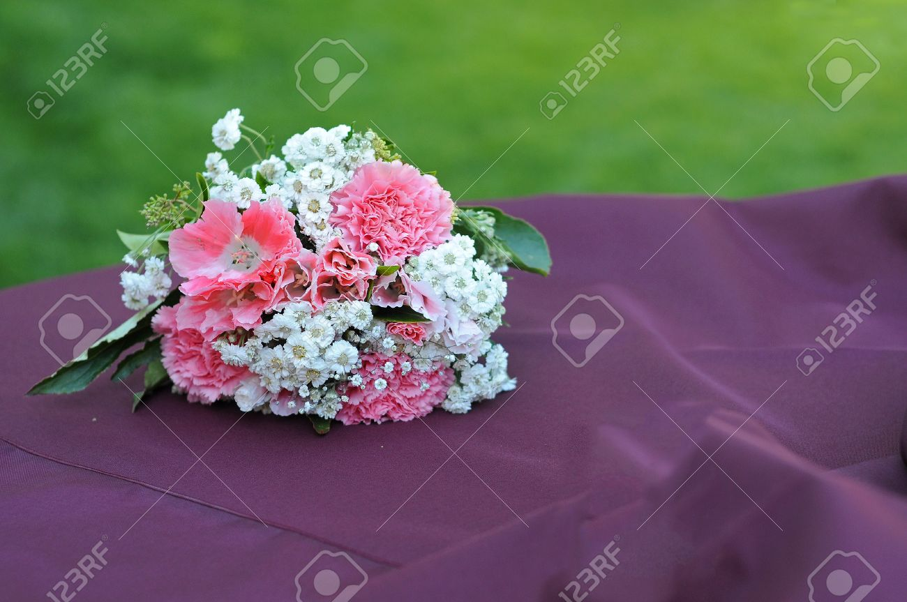 A bouquet of flowers resting on a table with grass copyspace above. Stock Photo - 7549916
