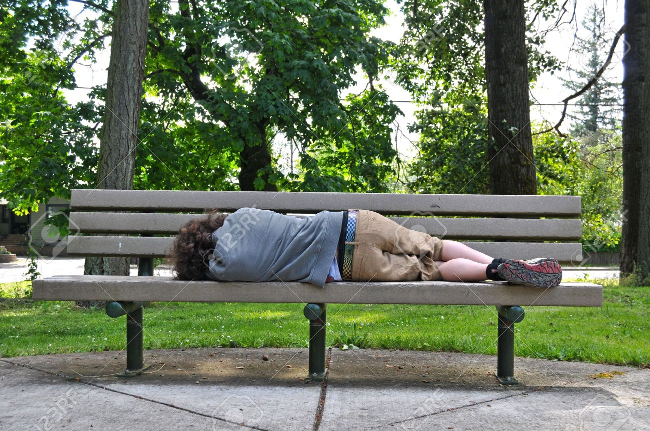 A homeless person takes a nap on a bench in a public park. Stock Photo - 7618057