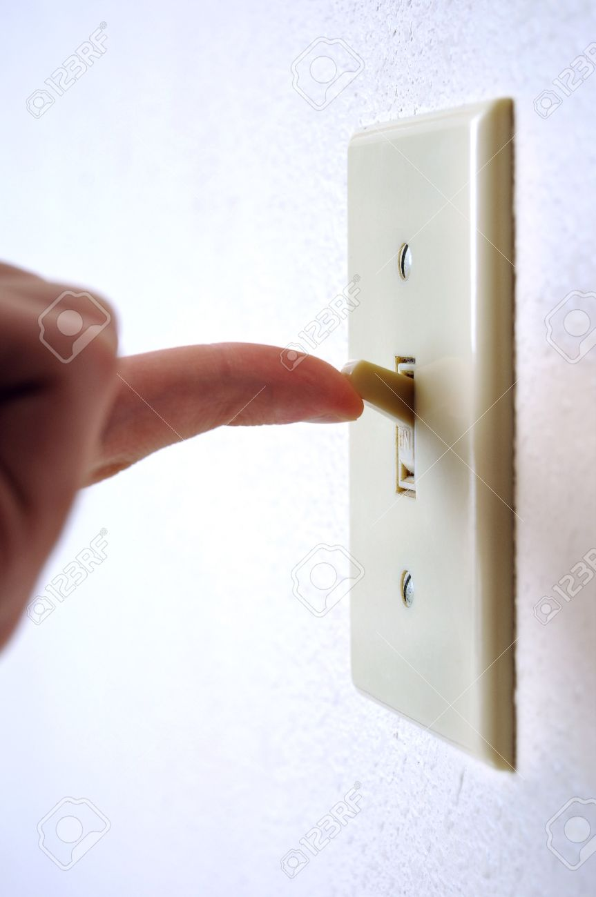 A Single Light Switch On A White Wall At An Angle With A Finger ...