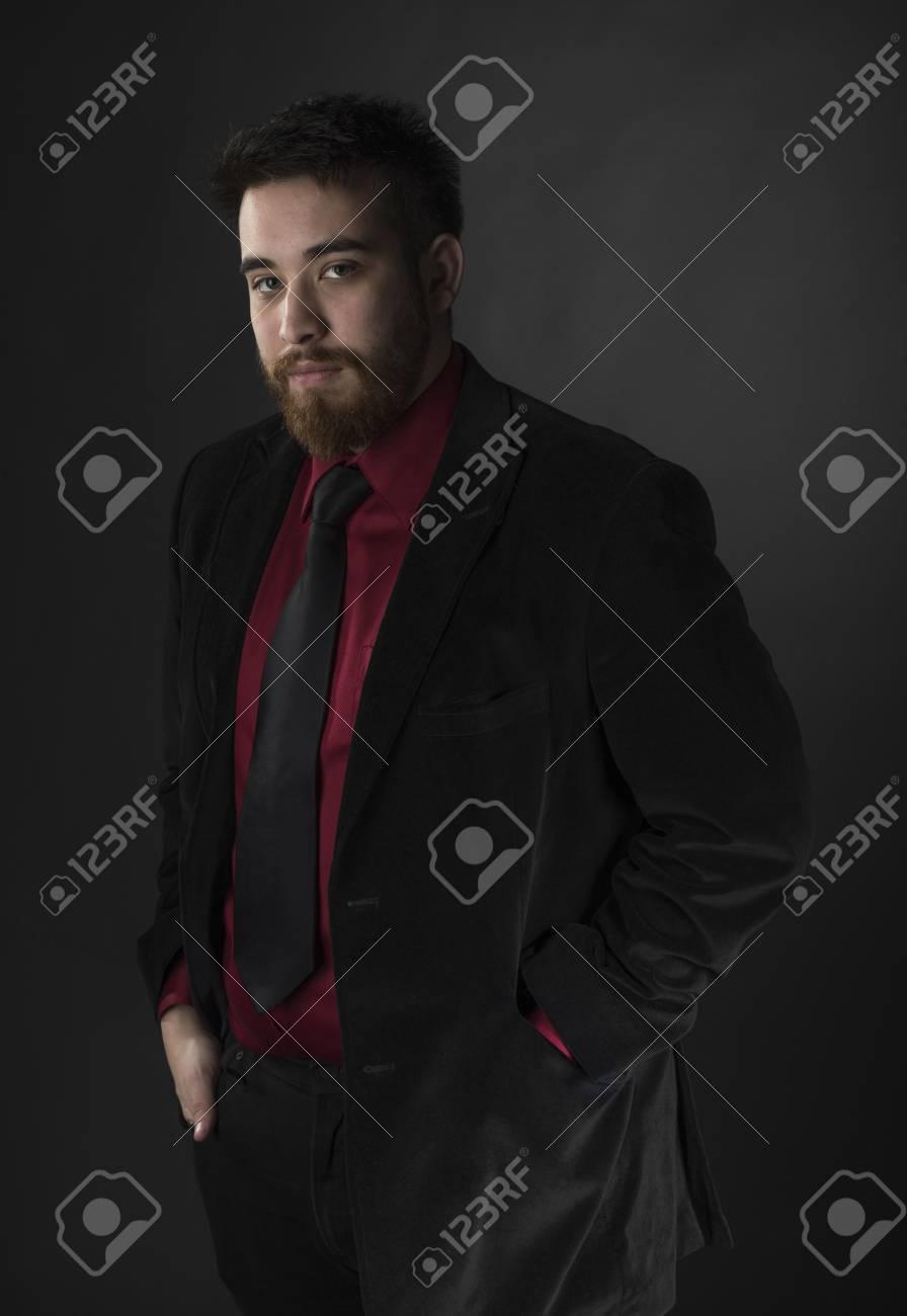 Foto de archivo - Joven Perilla del hombre que desgasta elegante marrón y Negro  traje formal mientras mira a la cámara. Aislado en el fondo Negro. 43a2c1cb2a7