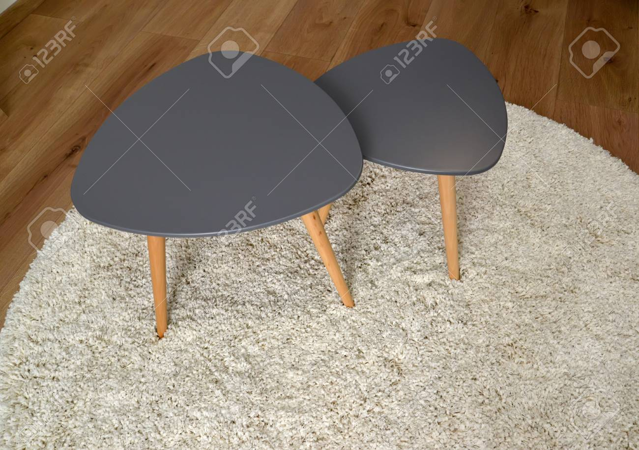 Two Coffee Tables Stand On A Round Rug Living Room Interior