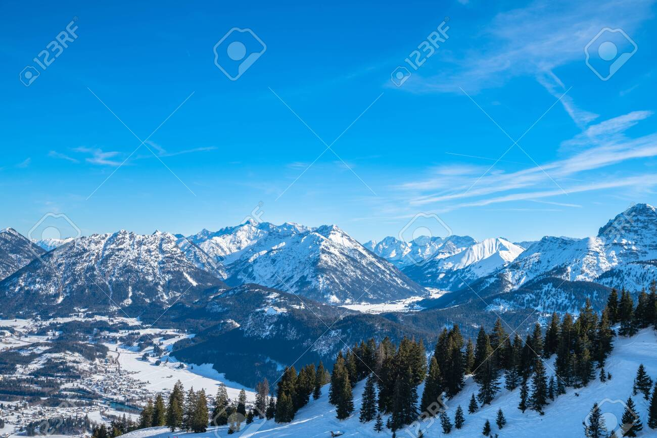 Panorama view of snow covered Austrian Alps in winter above the small town Reutte, with ski slope and skiing people in foreground, Tyrol, Austria - 151296832