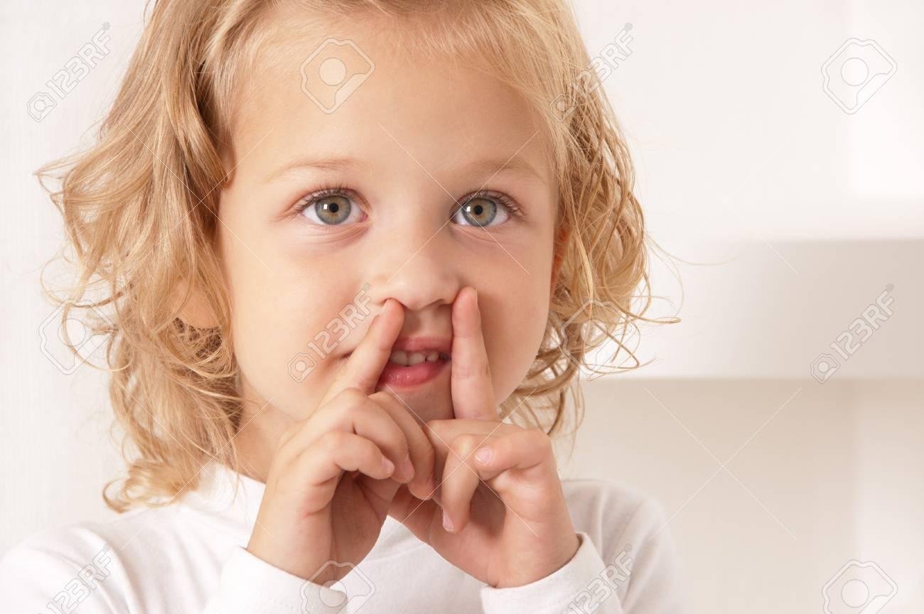 Blonde little girl  dressed in white standing and puts her fingers to her mouth in the form of letters