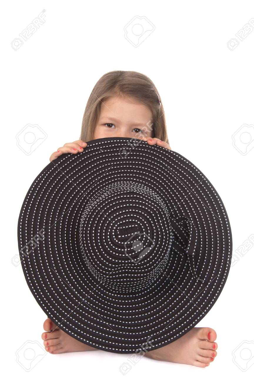 Cute smiling girl at the age of five hiding behind a big black hat on white background Stock Photo - 13785731