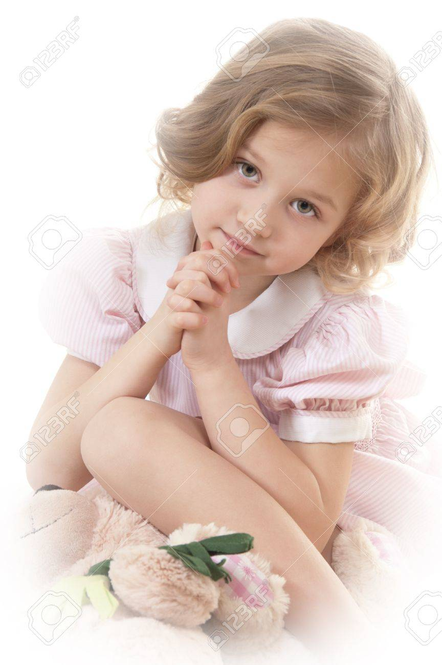 Sad adorable little blonde girl at the age of five wearing a pink dress sitting pensively on a white background and looking at the camera Stock Photo - 13952457