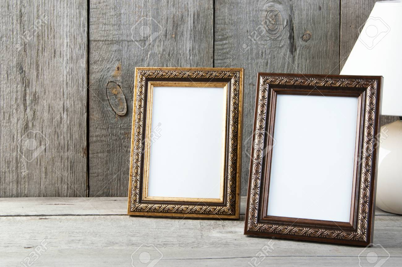 Two Empty Picture Frames And Table Lamp On Old Wooden Gray Textured