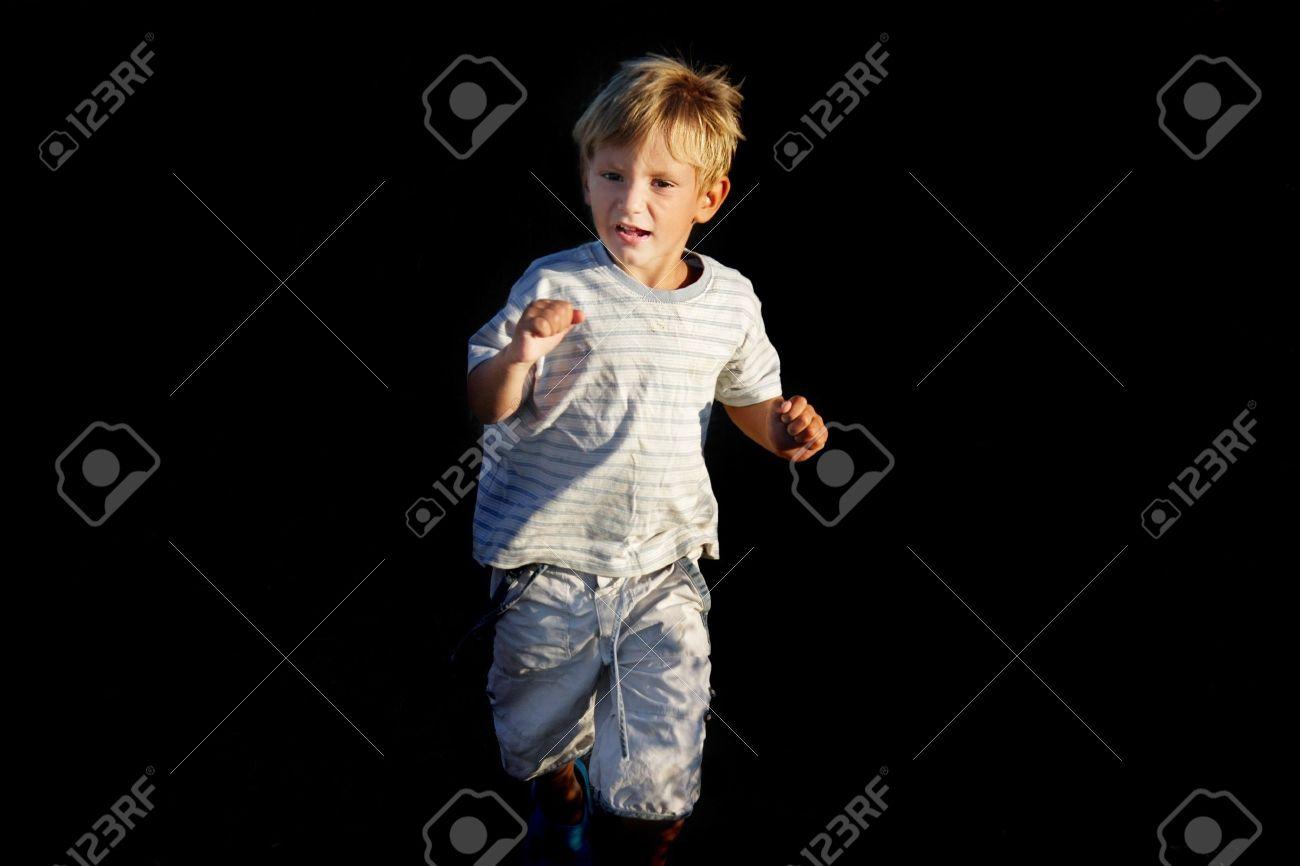 scared boy running away over black Stock Photo - 7786531