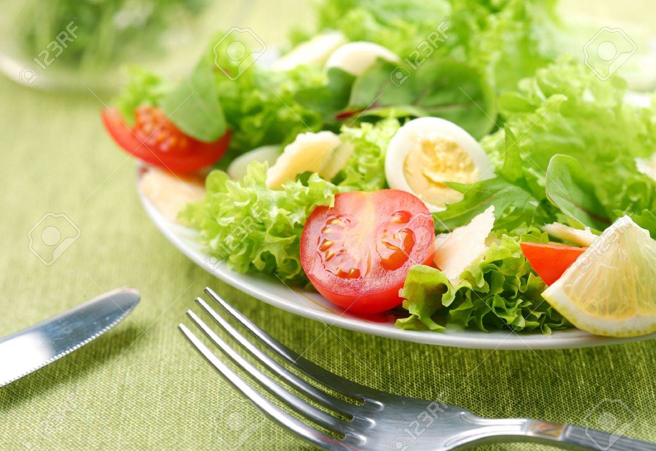 Fresh salad with tomato and quail eggs in a white bowl on a green tablecloth - 6608226