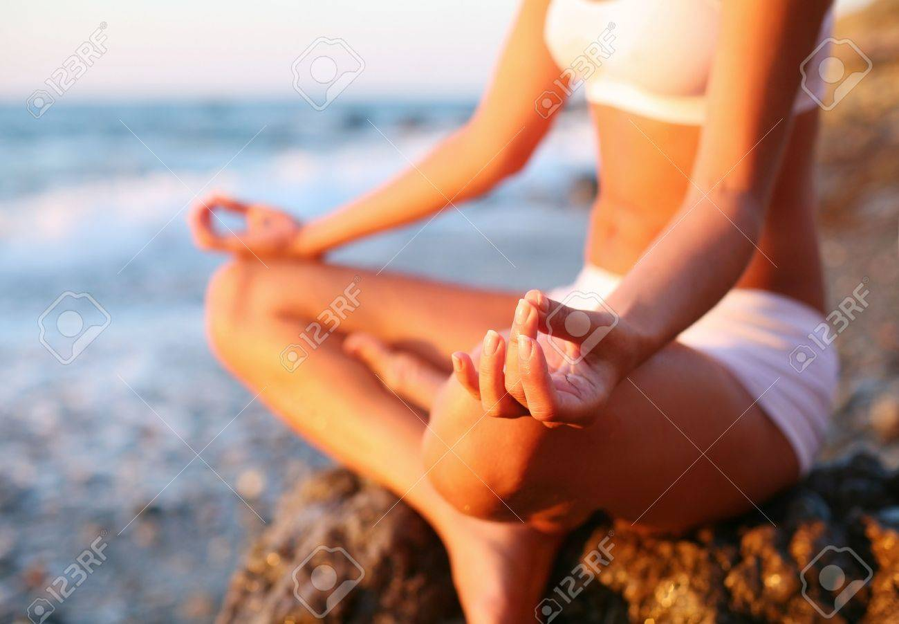 body of a beautiful girl in a meditation on the beach Stock Photo - 7734019