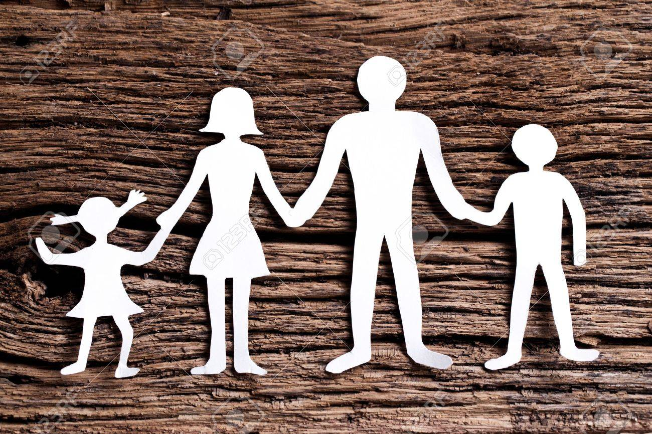 Cardboard Figures Of The Family On A Wooden Table The Symbol