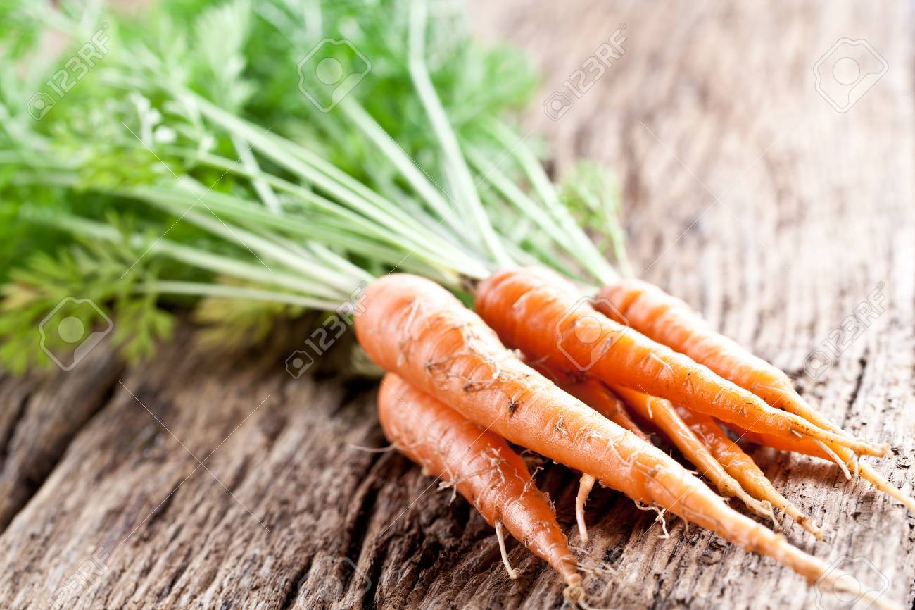 Carrots with leaves on a old wooden table. Stock Photo - 19841277