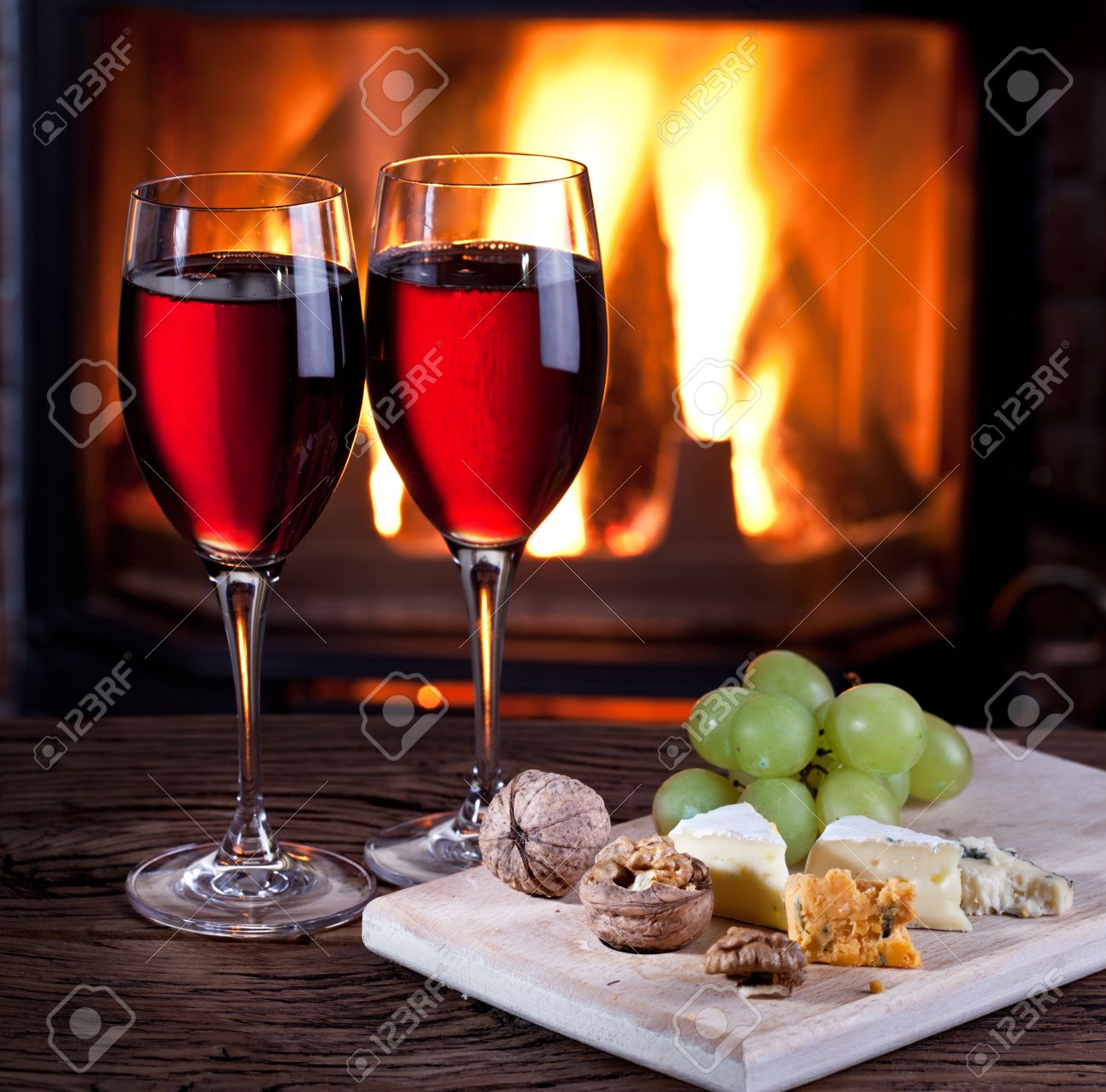 romantic still life near the fireplace glasses of wine cheese