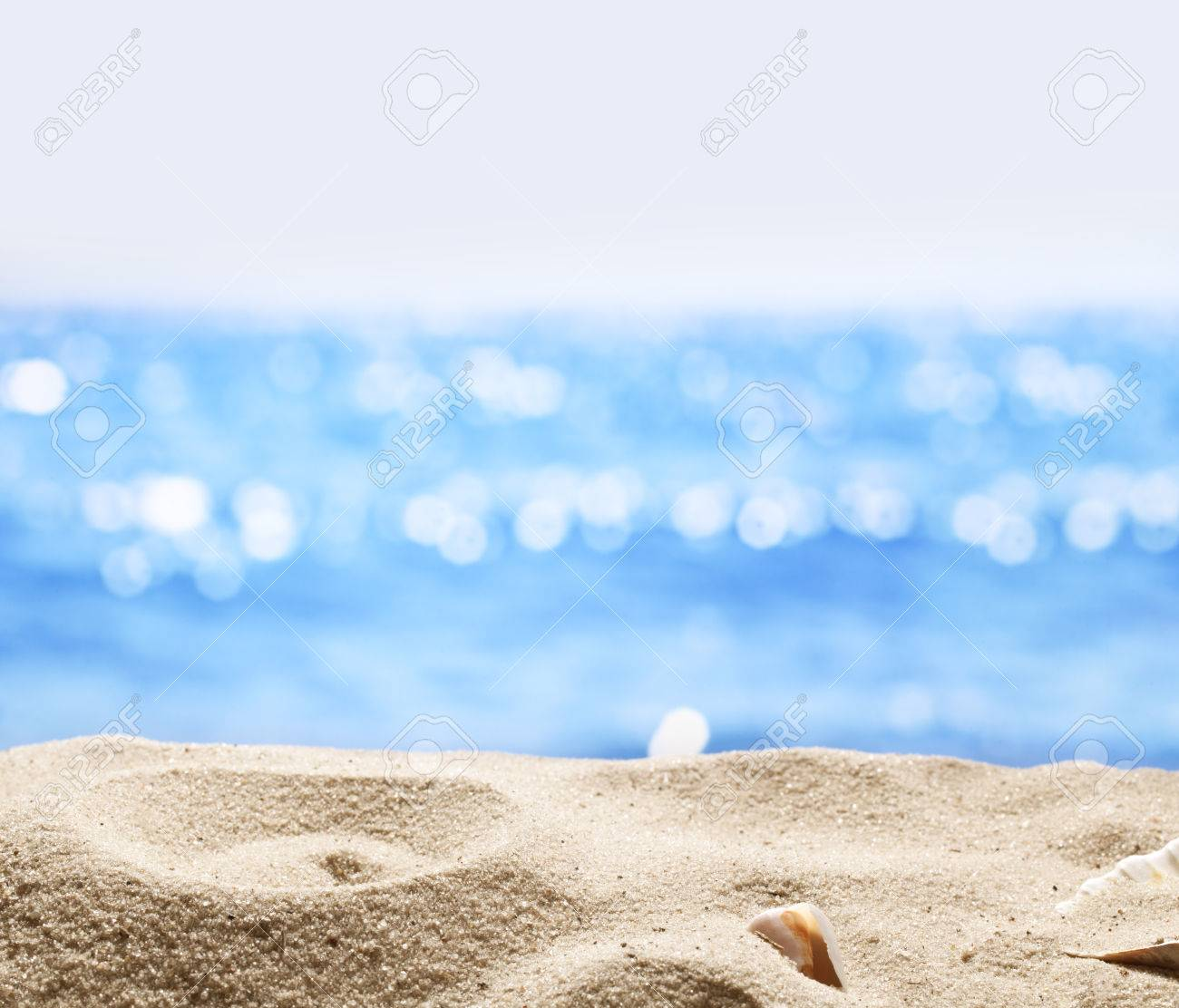 Sand with blurred sea background. File has clipping path for holes in the sand.