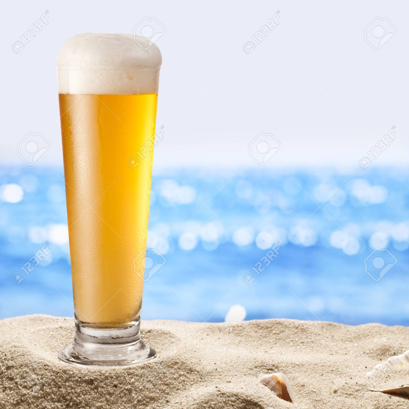 Photo of cold beer botle in the sand  Sparkling sea at the background