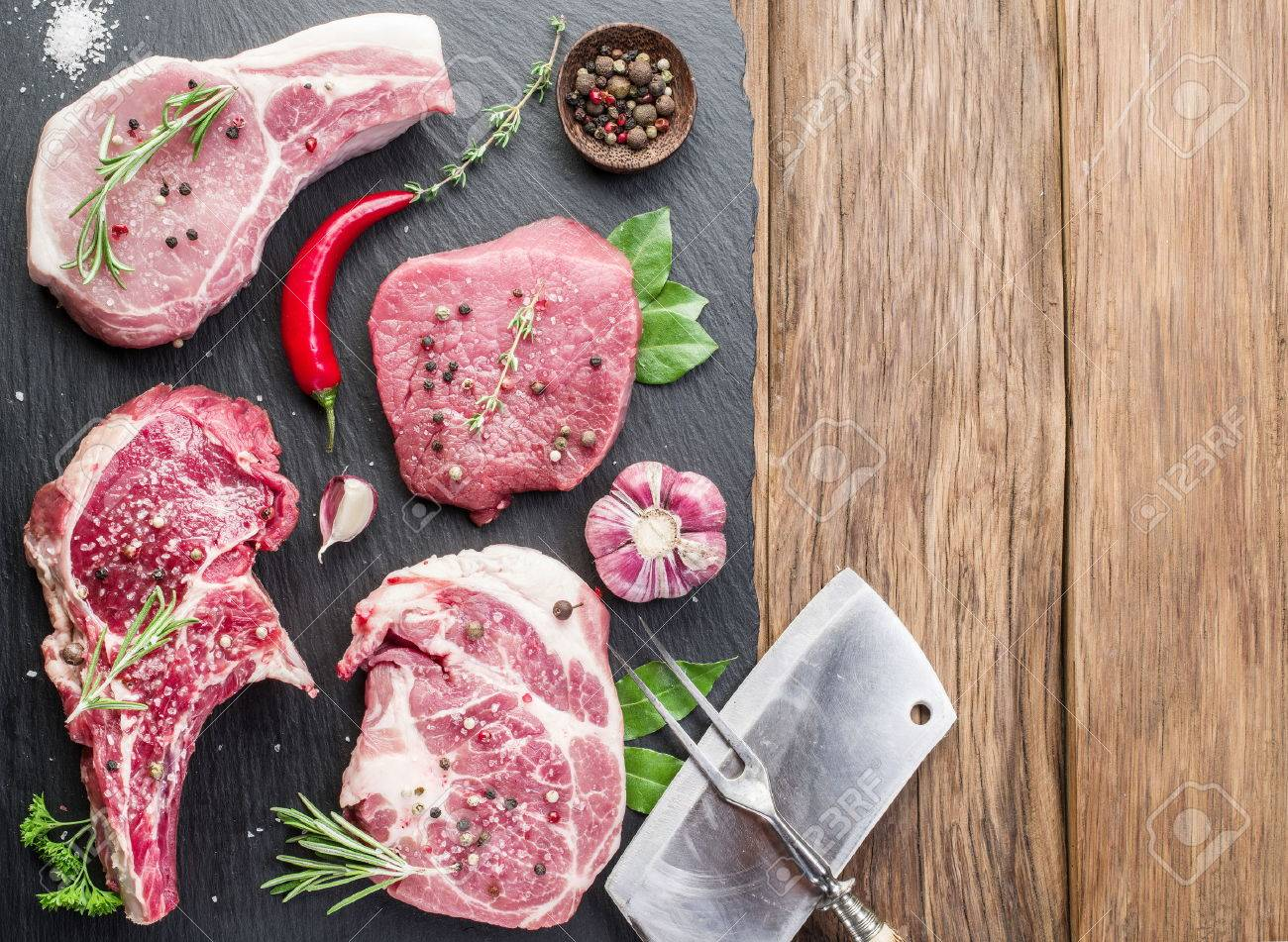 Raw meat steaks with spices on the wooden cutting board. Standard-Bild - 46222701