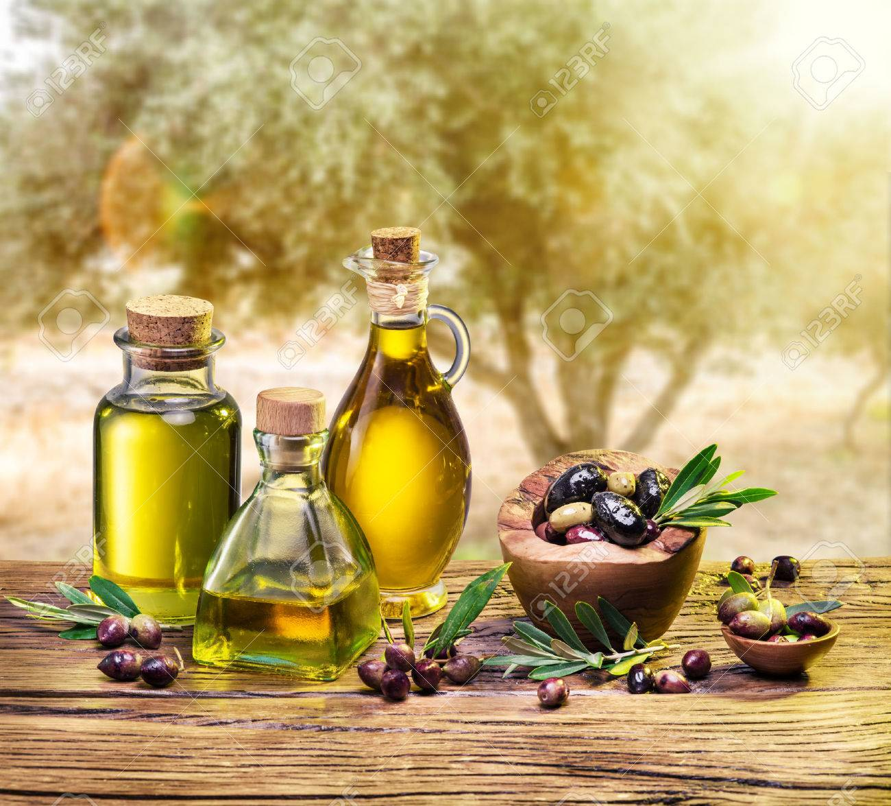 Olive oil and berries are on the wooden table under the olive tree. Standard-Bild - 49092144