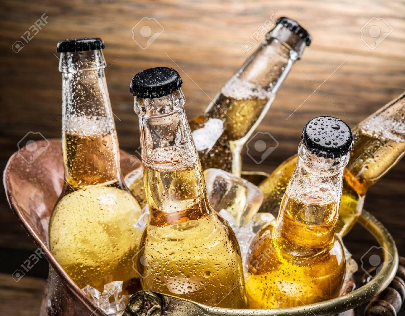 Cold bottles of beer in the brazen bucket on the wooden table. Standard-Bild - 53789489