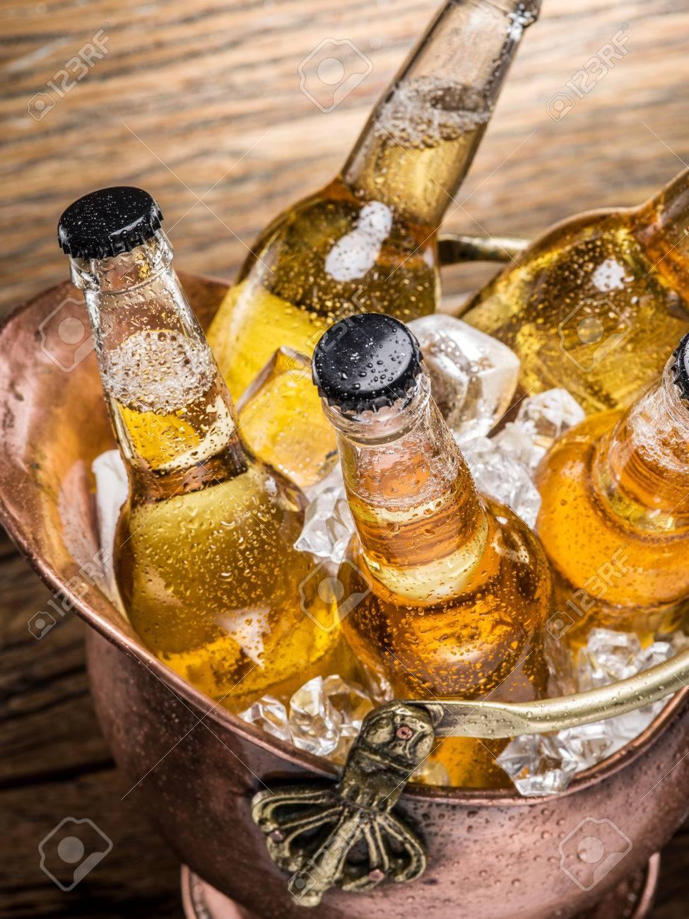 Cold bottles of beer in the brazen bucket on the wooden table. Standard-Bild - 55721153